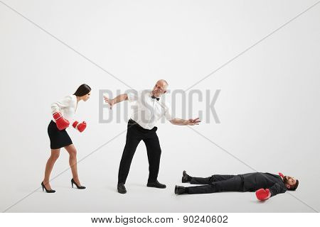 referee holding angry businesswoman in boxer gloves and counting down to knocked out businessman over light grey background