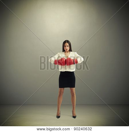 full length portrait of confided businesswoman in boxing gloves looking at camera over dark background