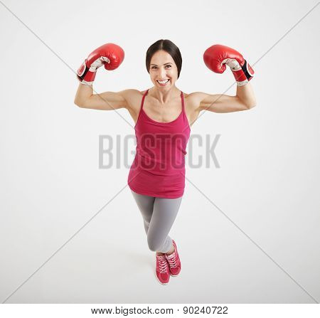 smiley sportswoman in red boxing gloves showing two biceps and looking at camera over light grey background