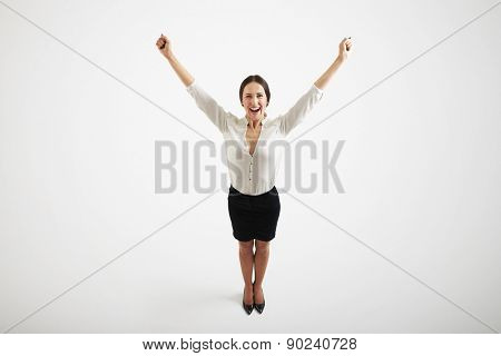 view from above of smiley woman in formal wear raising her hands up over light grey background