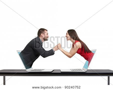 concept of love in social network. young man got out of the computer and holding hand of beautiful young woman who got out of another computer over white background