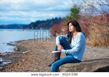 Young Teen Girl In Blue Shirt And Jeans Sitting Along Rocky Lake Shore
