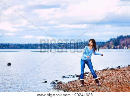 Teen Girl Throwing Rocks In The Water, Along A Rocky Lake Shore