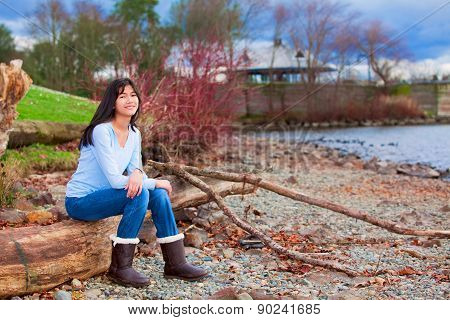 Young Teen Girl Sitting On Log Along Rocky Beach Of Lake