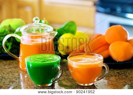 Two Cups Of Fresh Vegetable Juice On Kitchen Counter With Vegetables In Background