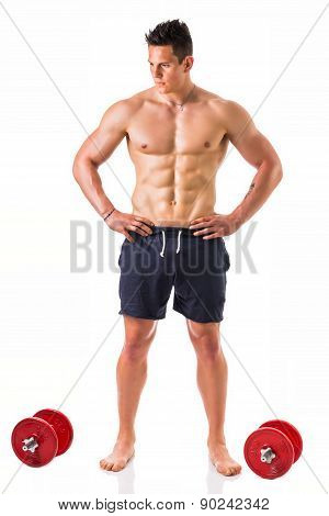 Handsome muscular shirtless young man holding dumbbells