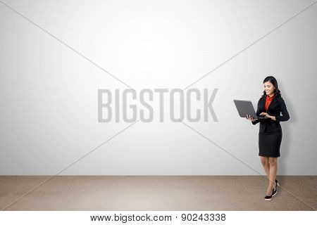 Woman Using Laptop With White Wall Background