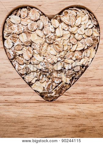 Oat Cereal Heart Shaped On Wooden Surface.