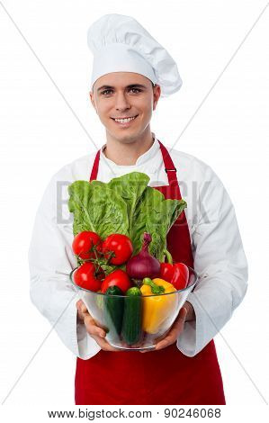 Male Chef Holding Glass Bowl Full Of Vegetables