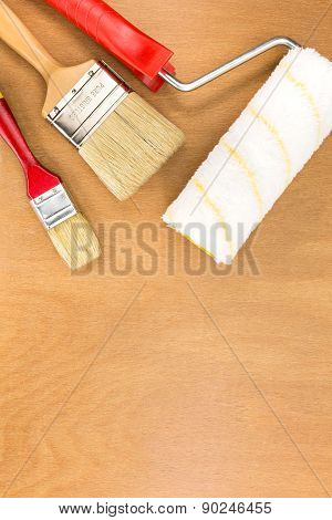 Paint Roller Tray With Brushes On Wooden Surface