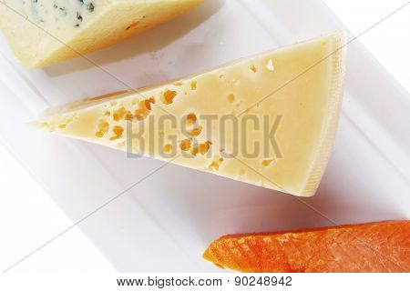 fresh aged french cheese parmesan roquefort and gruyere chops on white plate with isolated over white background