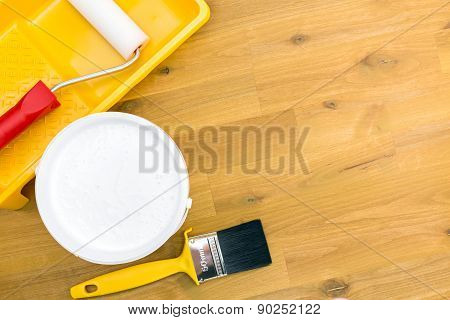 Paint Roller In Tray And Brush On Wooden Floor