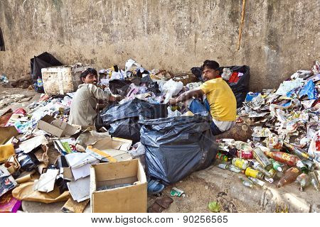 Poor Worker Checking Garbage For Plastic And Paper For Waste Separation
