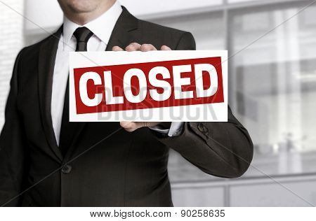 Businessman Holding Closed Sign To Viewer