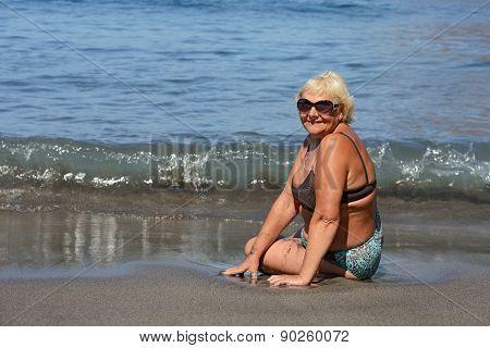 Aged Woman Is Sitting In Splashing Of Ocean Waves.