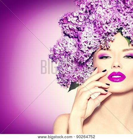Beauty fashion model Girl with Lilac Flowers Hair Style. Beautiful Model woman with Blooming flowers on her head. Nature Hairstyle. Summer. Holiday Creative Makeup and manicure. Make up. Vogue Style