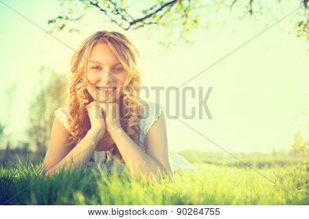 Beauty Romantic Girl lying on summer field Outdoors. Nature. Beautiful young Model Woman with long curly hair Smiling. Cute Teenage Girl lying on grass. Meadow. Grassland. Allergy free. Sunshine