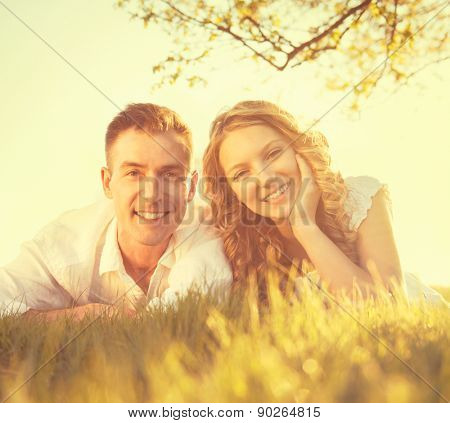 Happy Smiling Couple Together Relaxing on Grass in a Park. Young Man and Woman Lying on Grass Outdoor. Vacation concept. Summer Picnic. Summertime