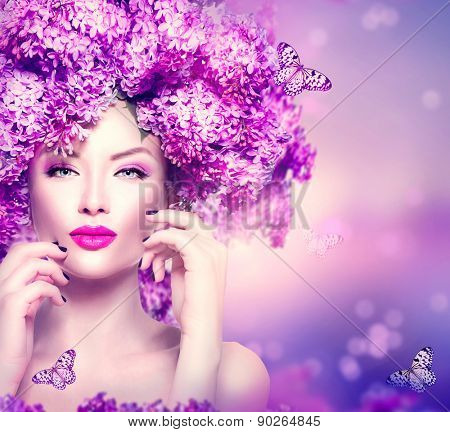 Beauty fashion model Girl with Lilac Flowers Hair Style. Beautiful Model woman on Blooming purple flowers background with butterfly. Nature Hairstyle. Holiday Makeup and manicure. Make up Vogue Style
