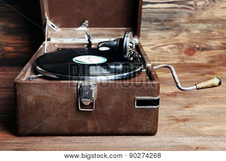 Vintage turntable vinyl record player on wooden background
