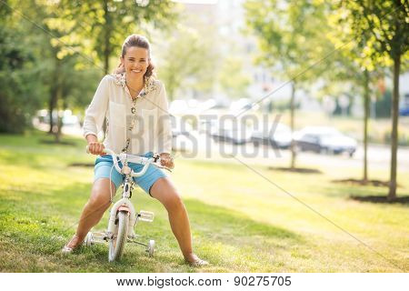 Mother Pretending To Ride A Child's Bike In A Sunny City Park