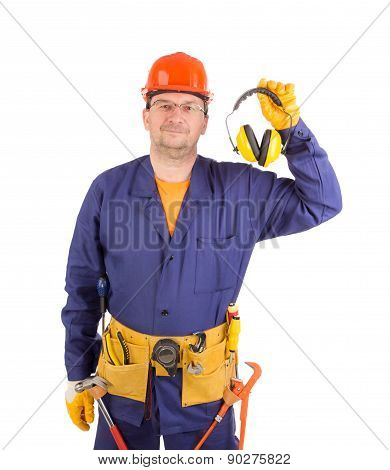Worker in hard hat holding ear muffs.