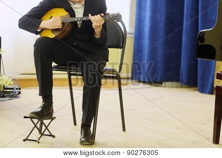 The performer plays a mandoline during a concert