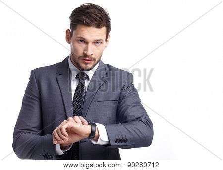 young businessman looking at watch over white background