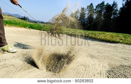 Golfer Hitting Out Of A Sand Trap. The Golf Course Is On The Sand. Sand Making Splashes