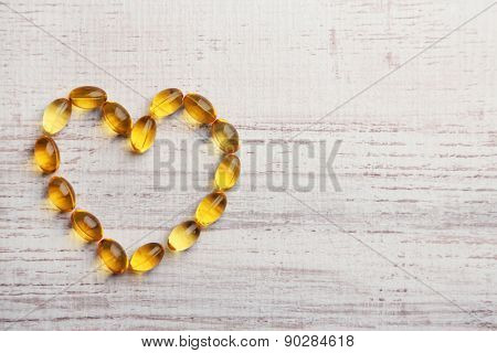 Heart of cod liver oil, on wooden background