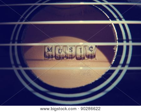 Letters of beads on a black ukulele on a white background