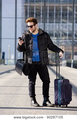 Happy Man Standing At Station With Bag And Mobile Phone