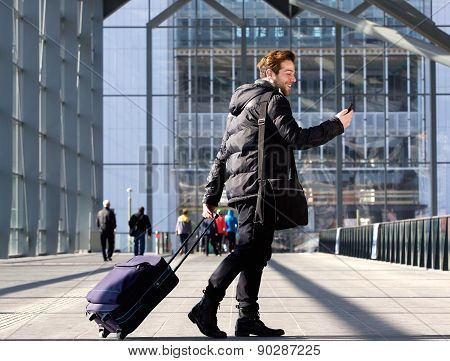 Man Walking With Suitcase And Looking At Mobile Phone
