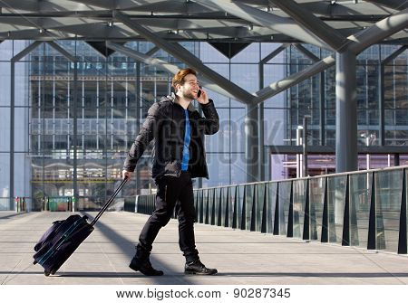 Man Walking With Suitcase And Mobile Phone At Airport
