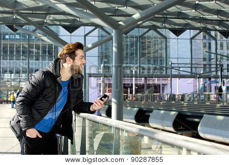 Cool Guy Standing With Mobile Phone At Train Station