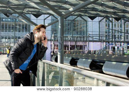 Smiling Man Talking On Mobile Phone At Station