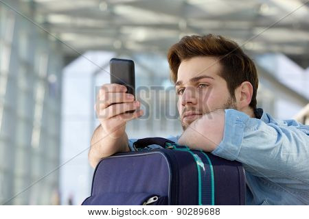 Traveling Man Waiting At Station And Looking At Mobile Phone