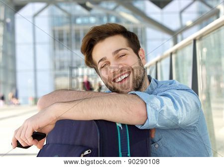 Cheerful Young Man Relaxing At Station With Bag