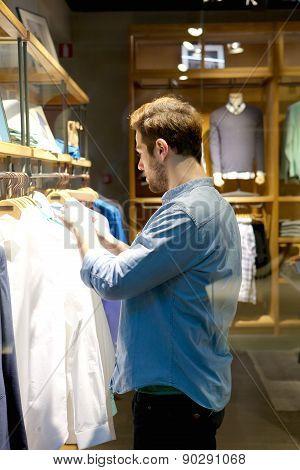Young Man Selecting Shirts To Buy At Shop