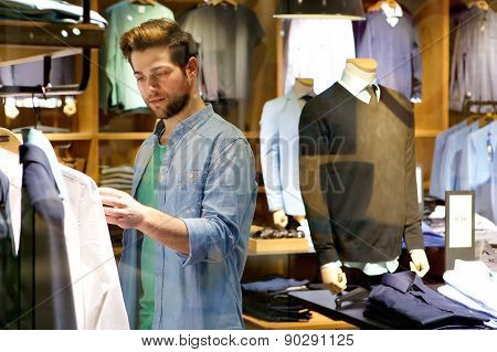 Young Man Looking At Clothes To Buy At Shop