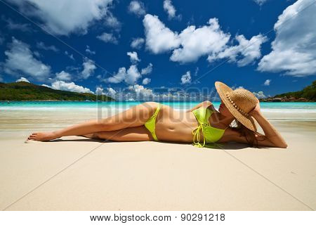 Woman in yellow bikini lying on tropical beach at Seychelles