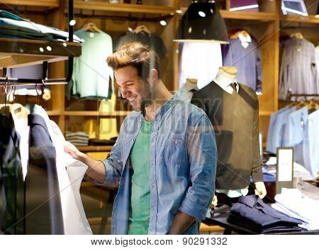 Smiling Man Shopping For Clothes At Clothing Store