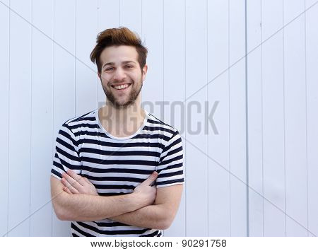Cute Guy Smiling With Arms Crossed On White Background