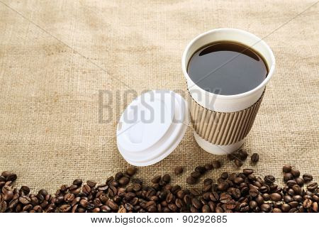 Paper cup of coffee with beans on sackcloth close up