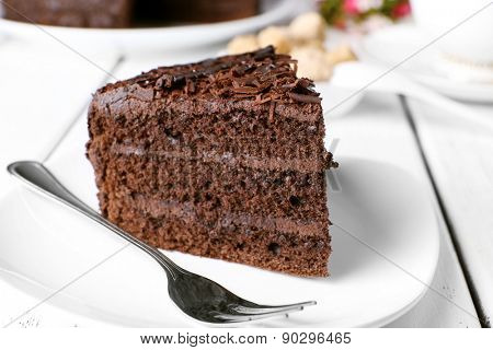 Piece of delicious chocolate cake in plate with fork on color wooden table background