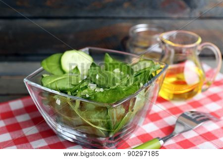 Glass bowl of green salad with cucumber and spinach on wooden table with napkin, closeup