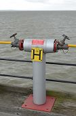 stock photo of jetties  - Twin outlet valve water fire hydrant on a wooden jetty - JPG