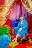 picture of harem  - Young oriental beauty sitting in a tent and holding a jug of wine - JPG
