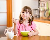 image of healthy eating girl  - kid girl eating healthy food in kitchen - JPG