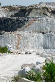 picture of open-pit mine  - The white chalky rock of a three tiered layered cliff at an open - JPG